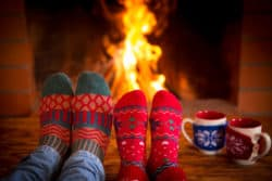tips for a less stressful holiday, relaxing around the fire in socks with hot chocolate